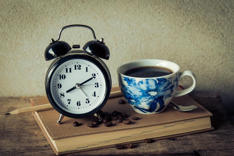 Alarm clock plus coffee, on top of a book!
