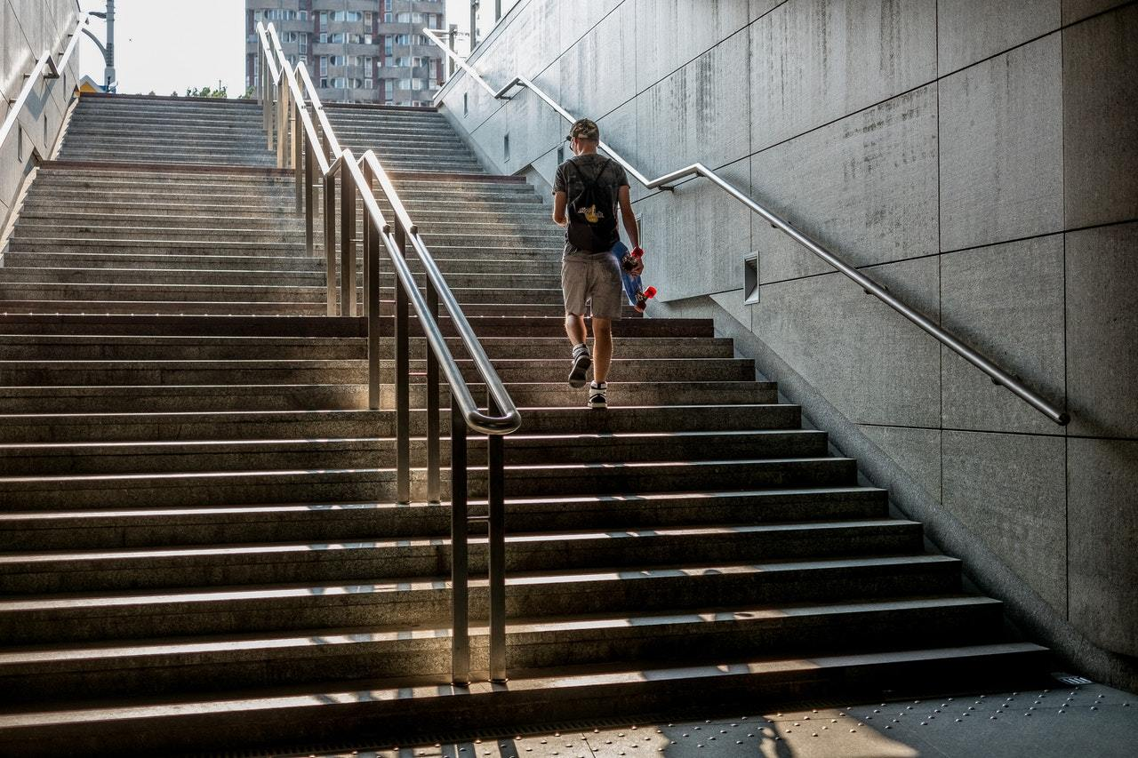 a man walking up the staircase from a metro to the street