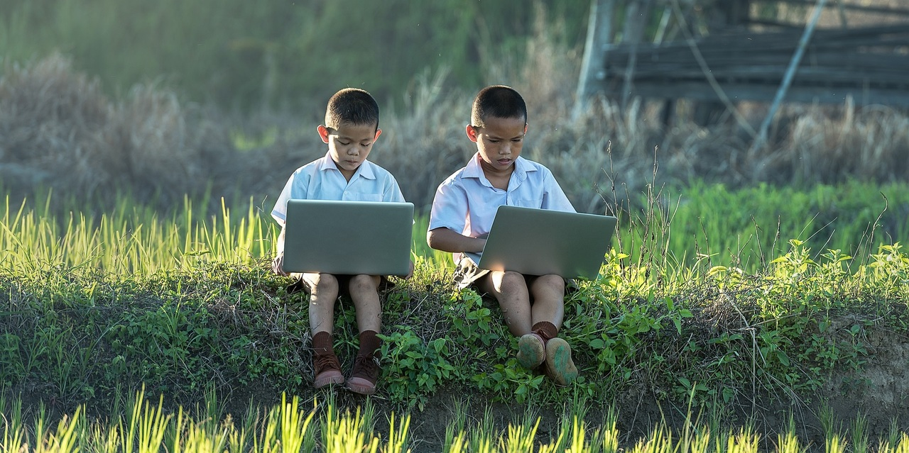 two boys sitting and using their laptops