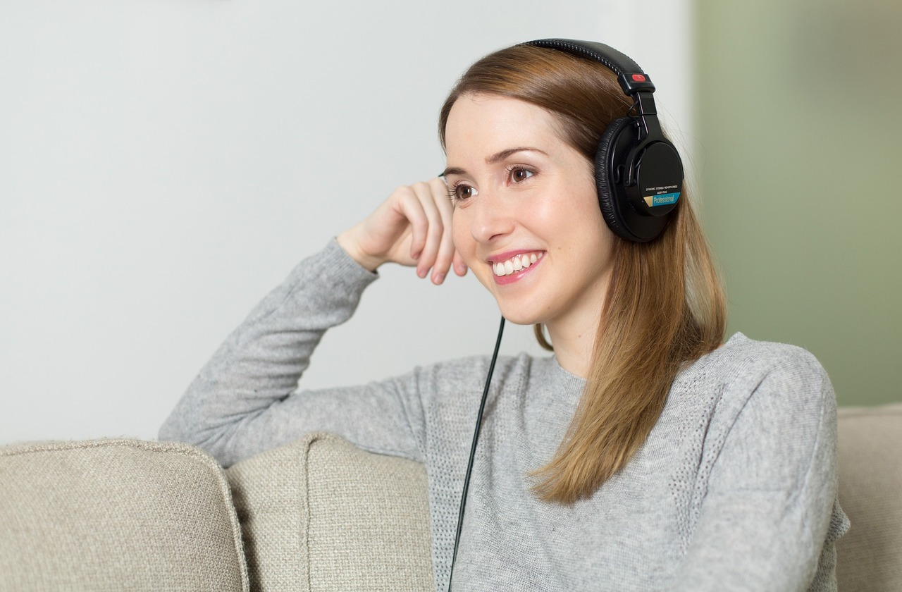 girl sitting with headphones on listening to music