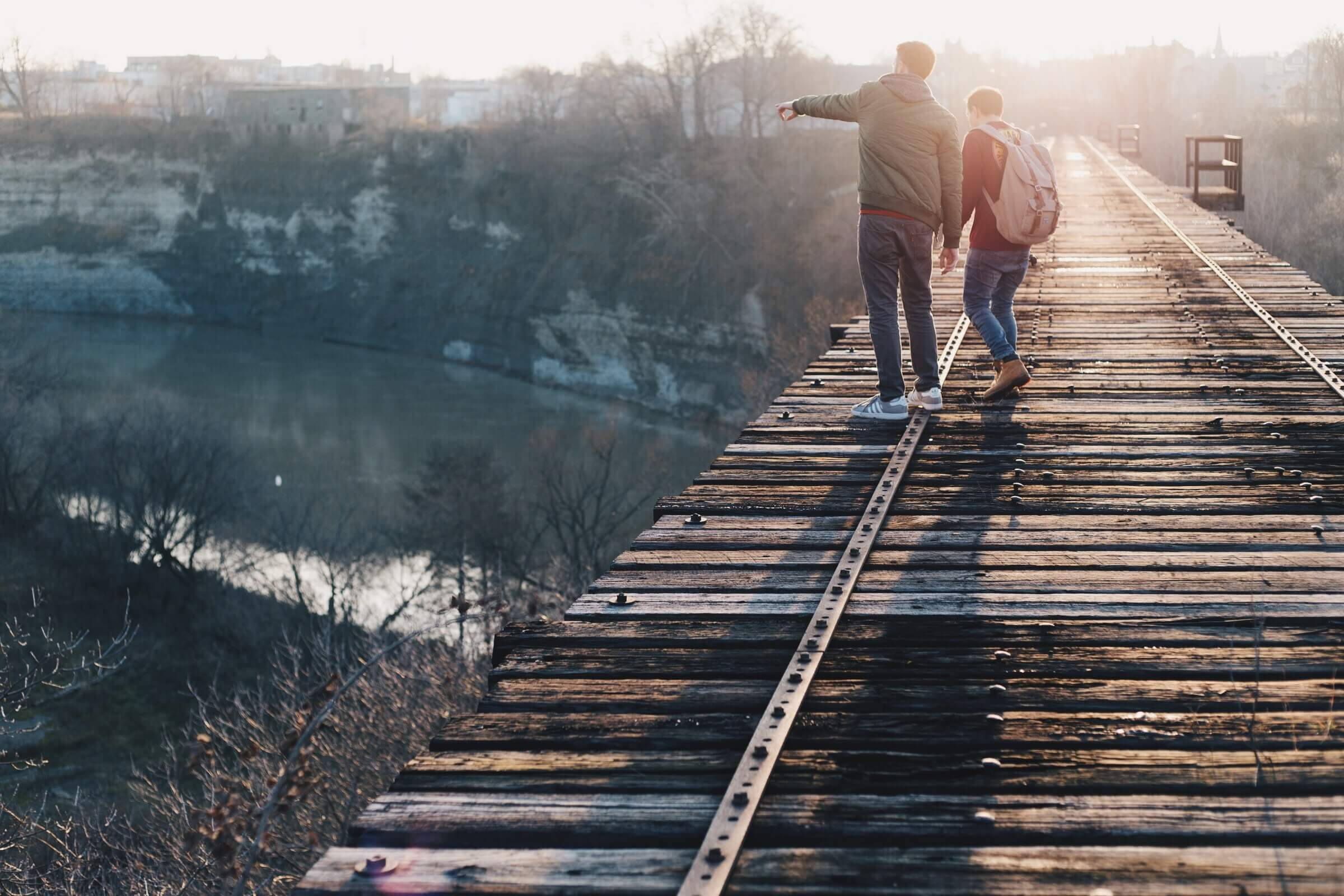 two boys hanging out on a bridge