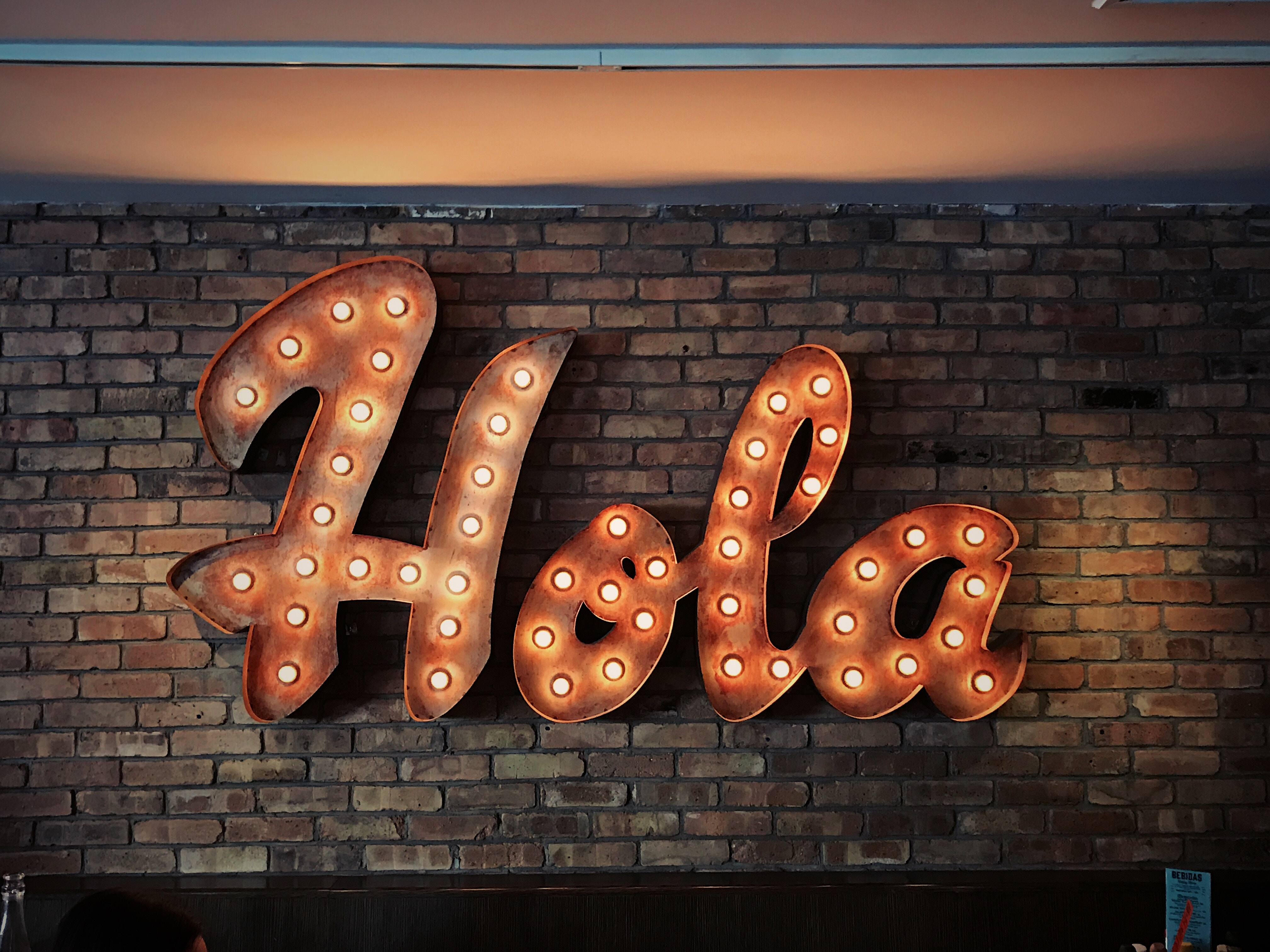 """Bright light bulbs in a sign reading """"Hola"""" on a brick wall"""