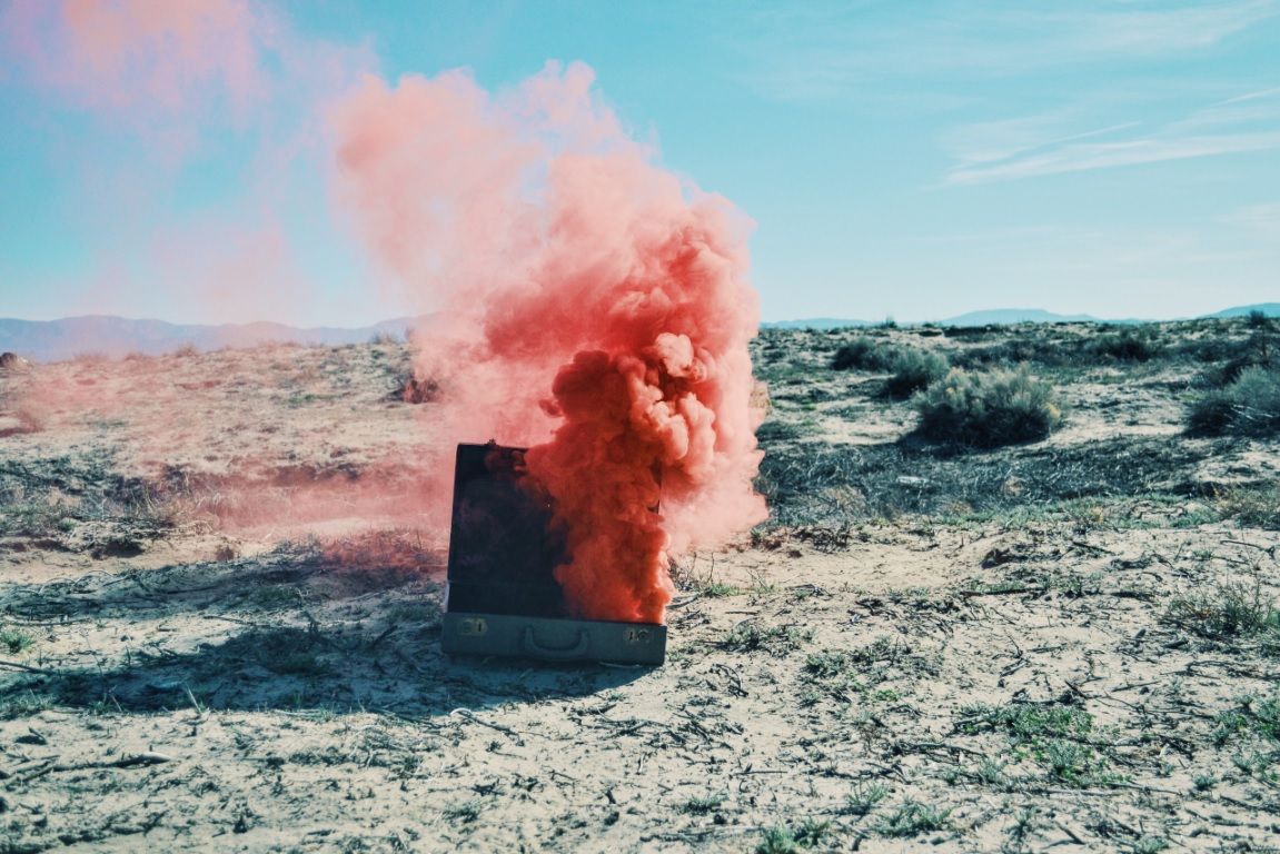 red smoke blowing out of a suitcase