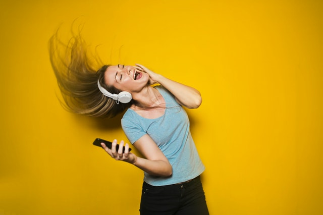 a girl listening to music and flipping hair