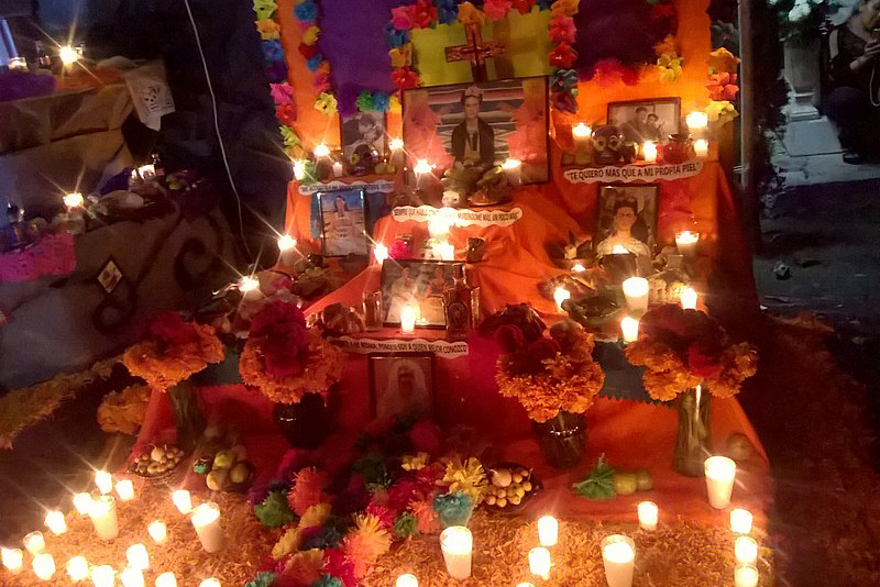 day of the dead altar at night with candles