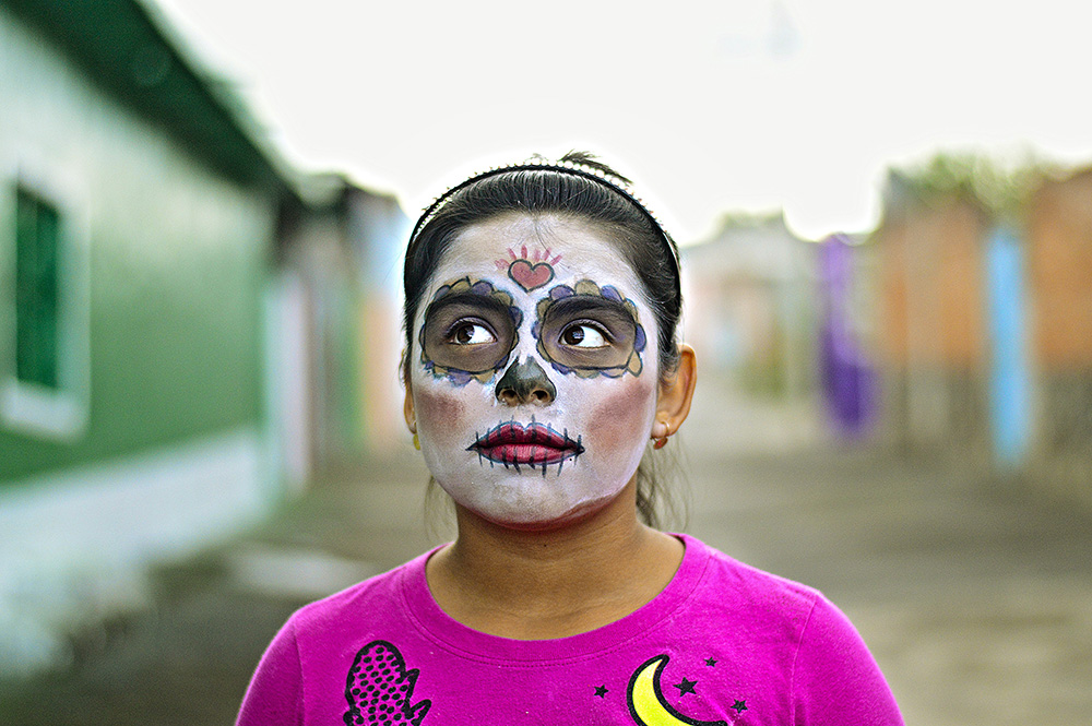 little girl with day of the dead makeup in town