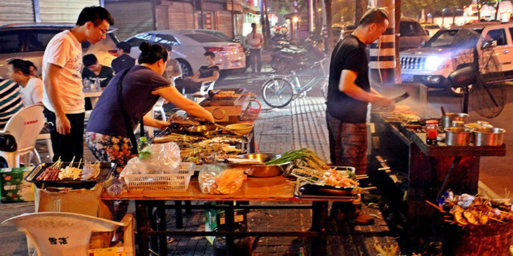 Three people preparing and grilling Chinese barbeque on the street