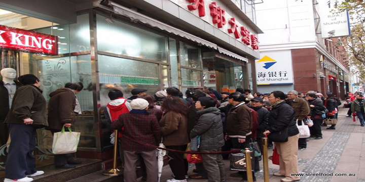 Chinese people queueing for food on a street in Shanghai