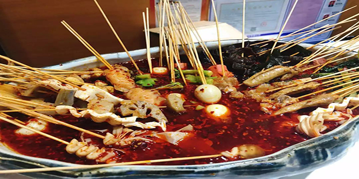 Skewers of meat and vegetables including eggs, lotus root, tofu and mushroom in a bowl of spicy red oil