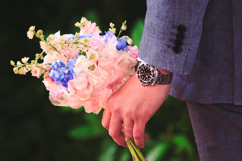 Man With Watch Holding Flowers
