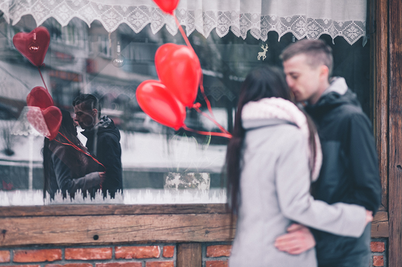 People Kissing on Valentines Day in Front of Shop
