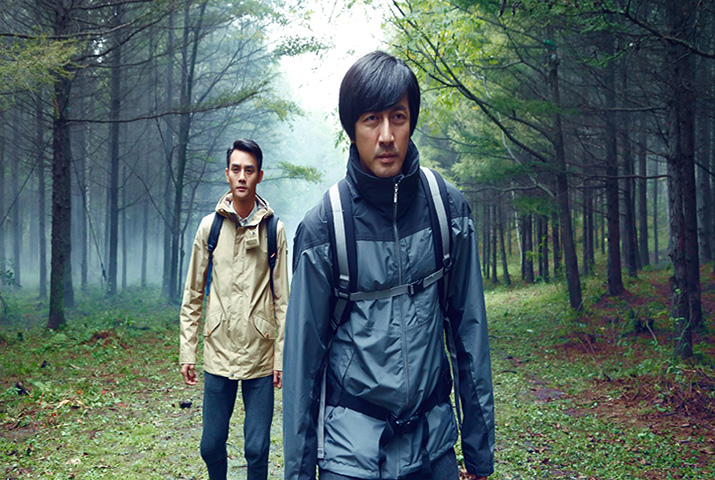 Two Asian men wearing rain jackets walkning on forest path