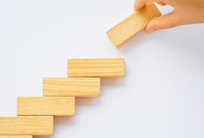 Person with white hand placing one wooden block on top of five others in a stair formation.