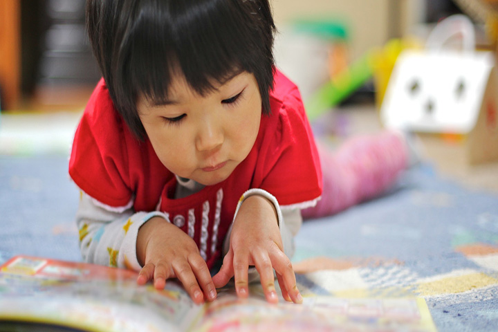 Asian child in red t-shirt reading on the floor