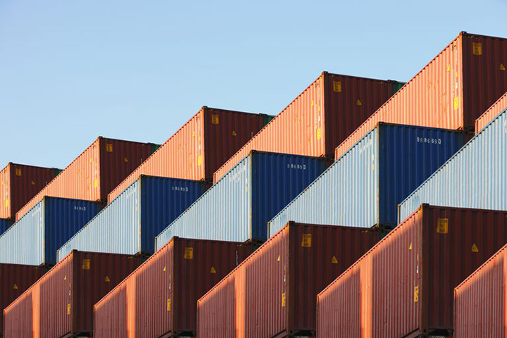 Three rows or brown, blue and red frieght containers under a blue sky