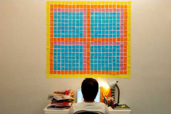Boy looking at desk looking at wall with post-it notes forming shape of a window