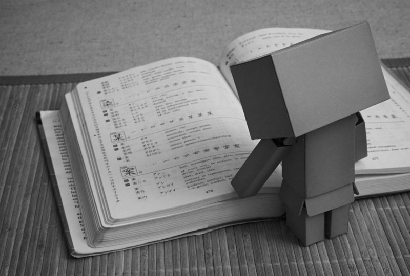 Cardboard robot reading Kodansha Kanji Learner's Course