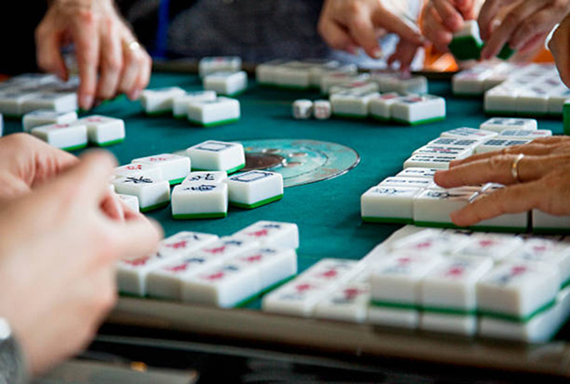 Four pair of hands playing with white and green tiles at a table with green felt cover