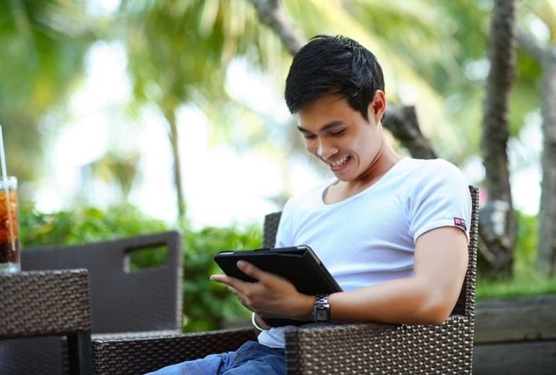 A young man happily using an app