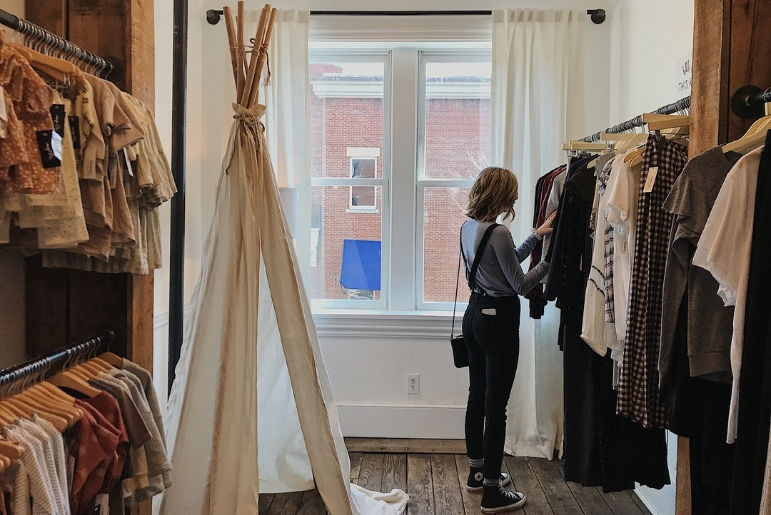 Woman-Standing-Selecting-Clothes-in-Store