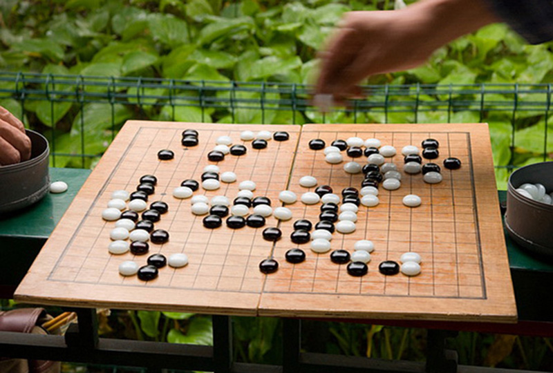 White and black pebbles on a brown wooden board with black squares in a garden