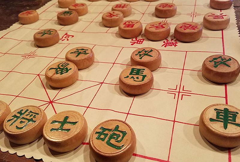 Circular wooden blocks decorated with green and red Chinese characters on a white mat with red squares on