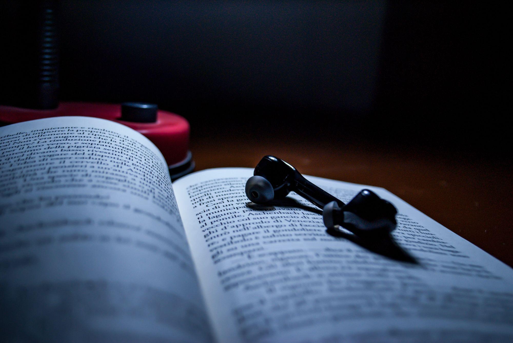 Earphones on top of a book