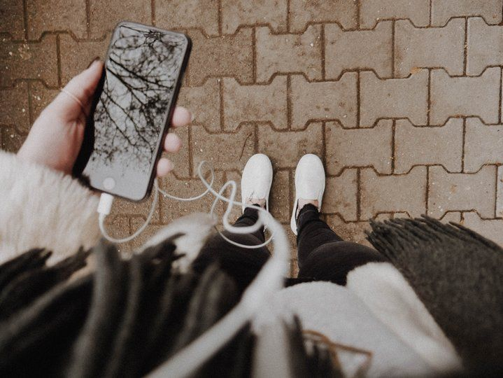 An iPhone with earphones in hands of a person