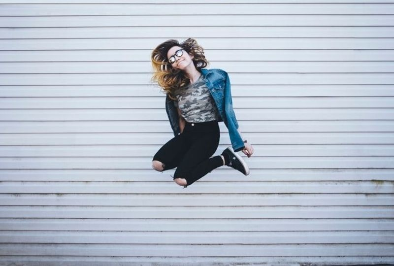 a girl shows positive attitude by jumping