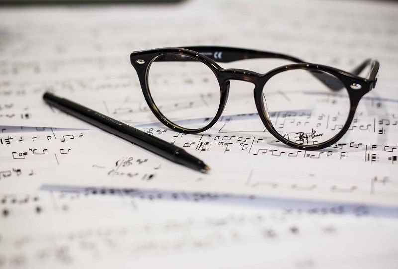 A pair of glasses sitting on some sheet music