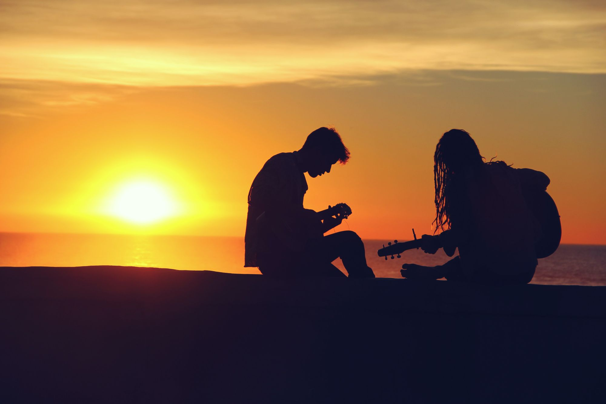 Two people playing the guitar on a beach while the sun sets