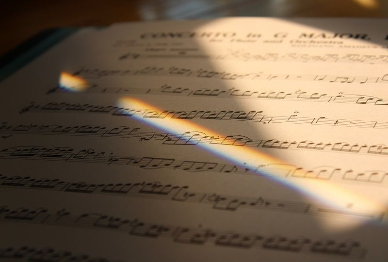 An extreme close up of sheet music in deep shadow