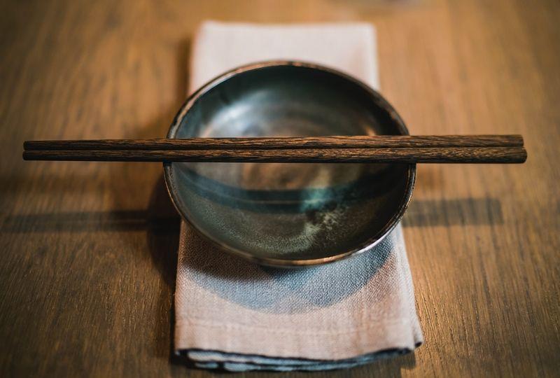 Chopsticks resting on an empty bowl