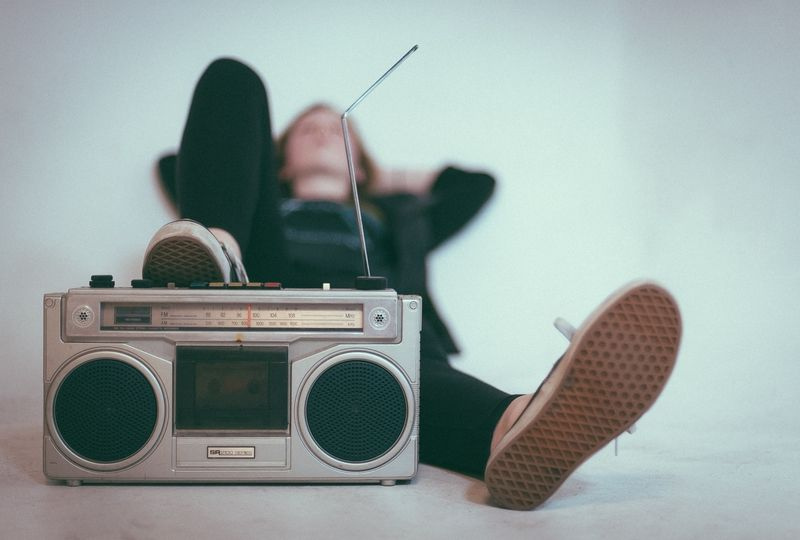 Person lying with foot on radio