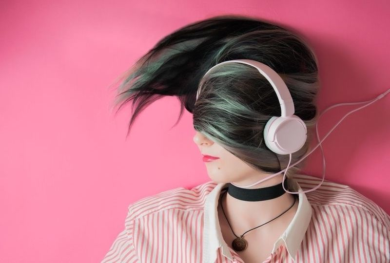 A girl laying down with headphone on