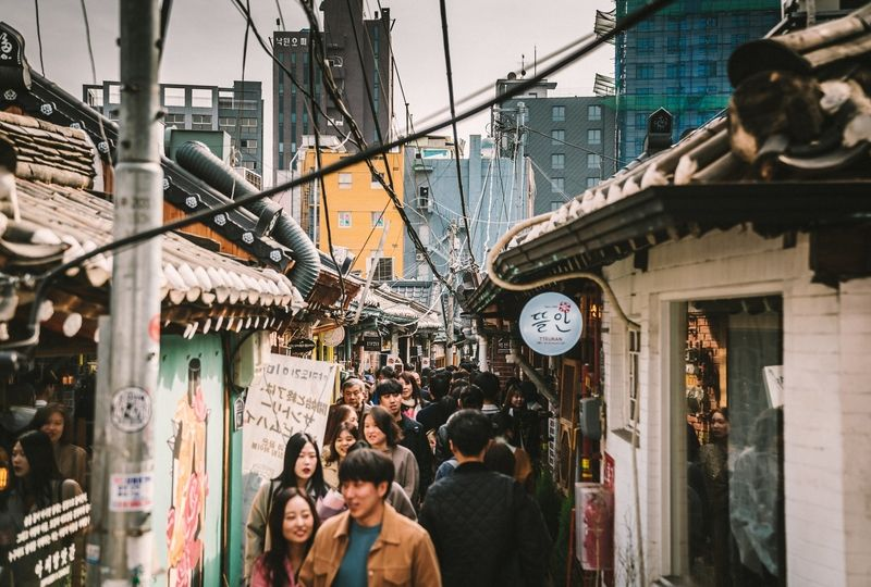 Koreans walking down a crowded alleyway