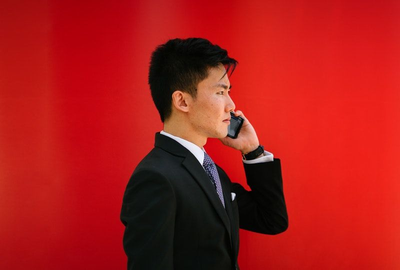 man holding smartphone wearing suit