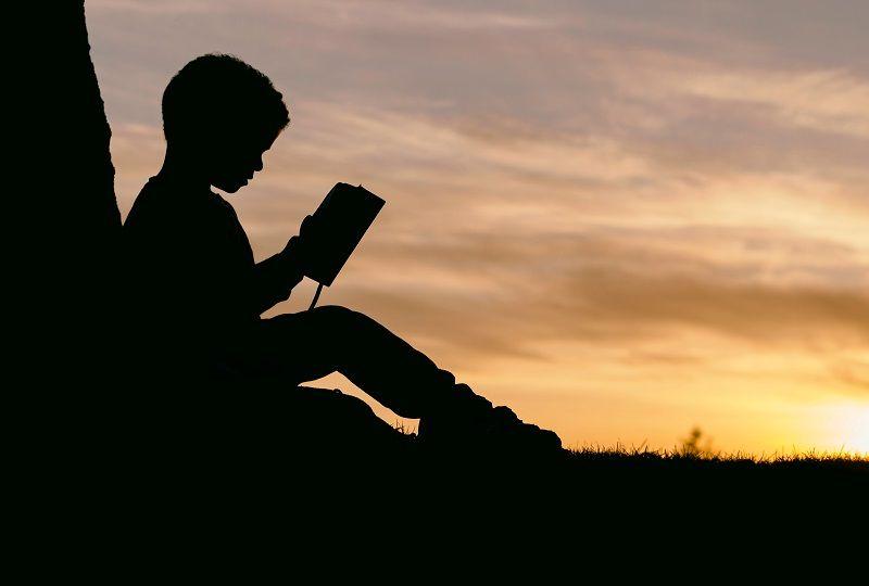 Boy on a mountain reading about Italian grammar
