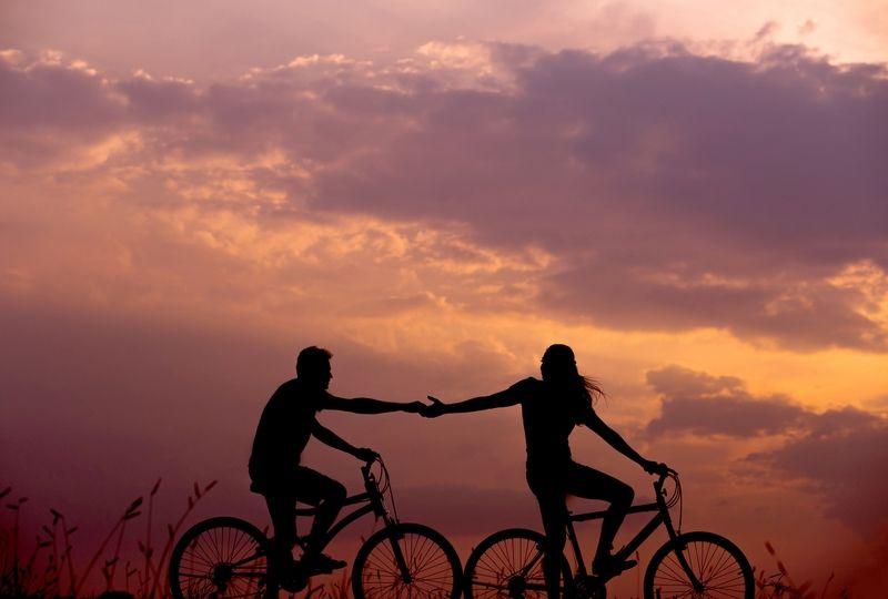 Couple riding bikes during sunset