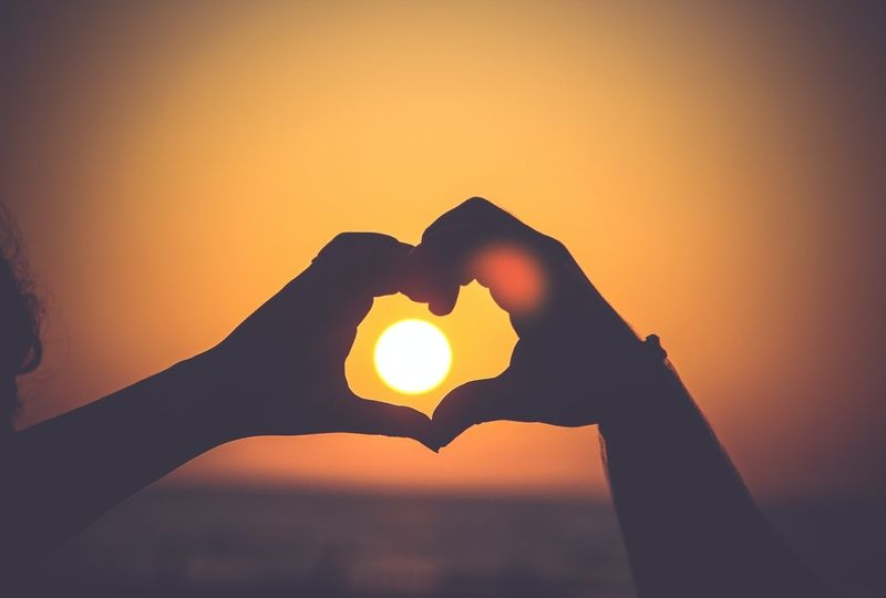 Hands making heart shape around the sun