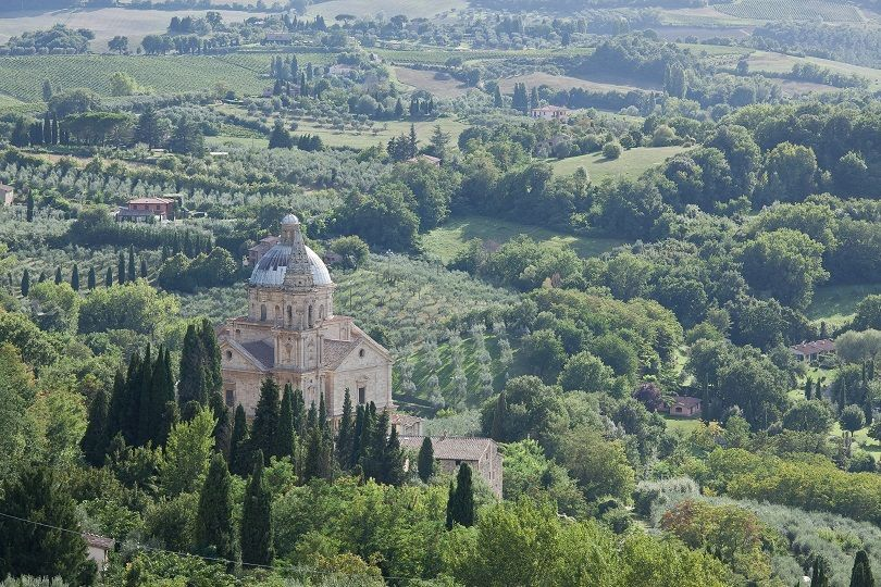 A view of the Italian countryside with a building in the foreground