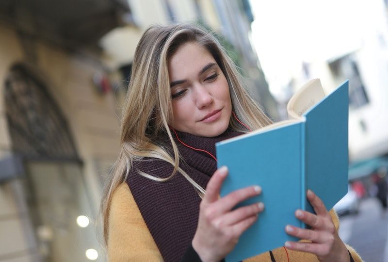 woman smiling and reading outside