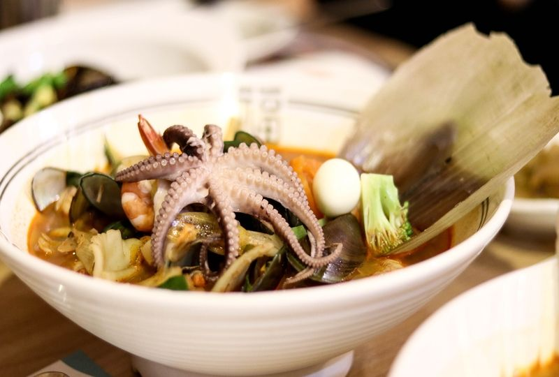 Octopus soup in white bowl