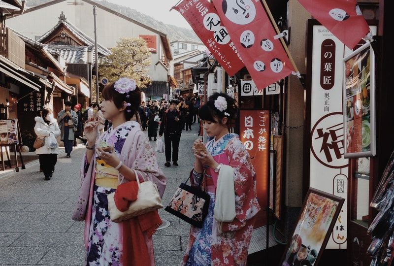women in kimonos come out of a shop