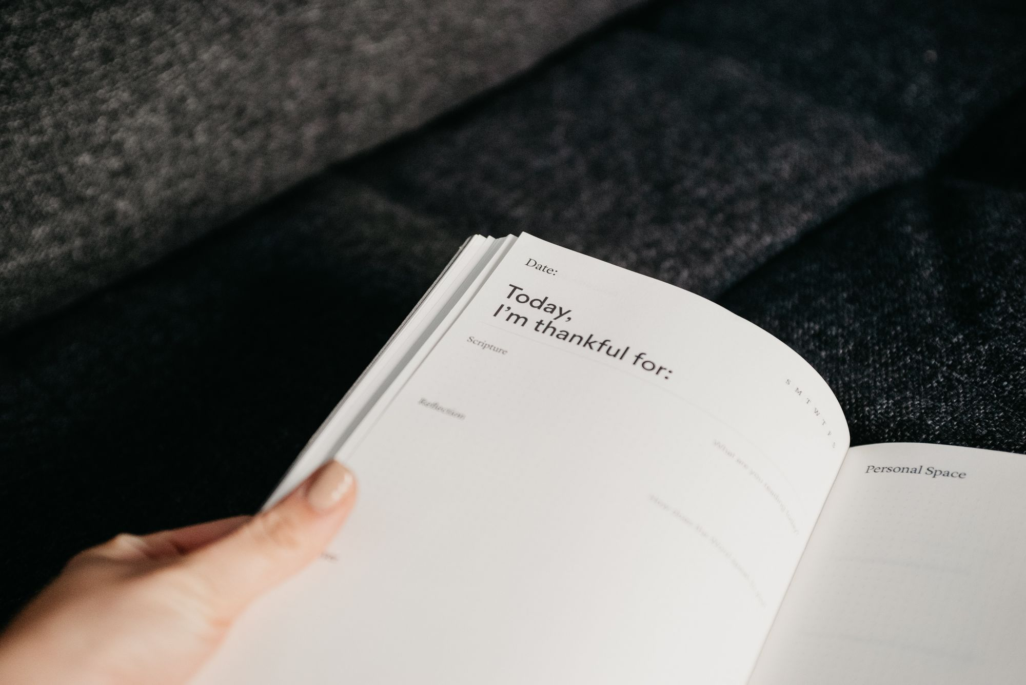 book on a table with a hand