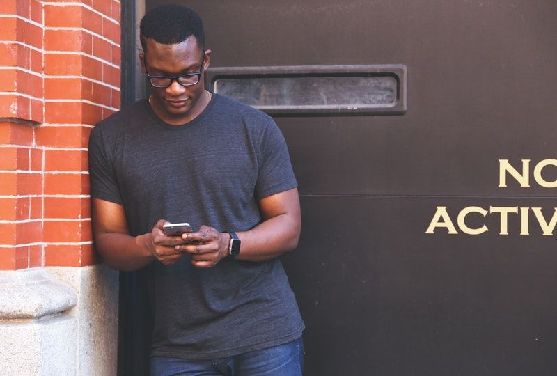 man using smartphone next to a brick building