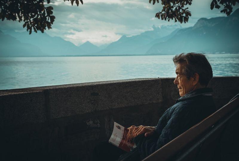A Man Sits on a Chair Near a Lake