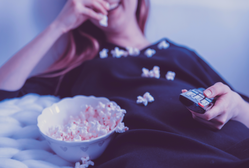 Woman eating popcorn and holding television remote