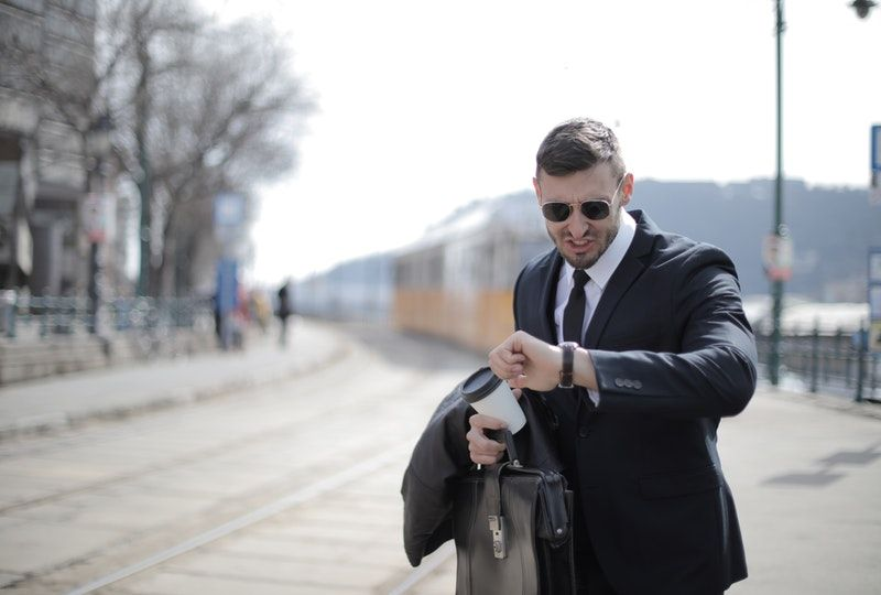 Business man at train station looks at watch
