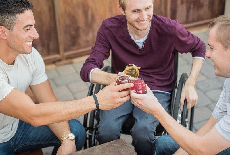 three friends enjoy drinks outside